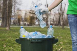 zdjęcie przedstawia osobę wyrzucającą plastikowe butelki do kosza - recycling, harmonogram odbioru odpadów komunalnych